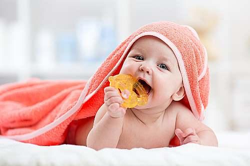 dziecko trzyma zabawkę w buzi