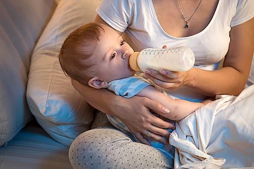 Mama karmi dziecko butelka po odstawieniu od karmienia piersią.