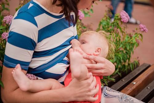 Mama karmi dziecko piersią w miejscu publicznym.
