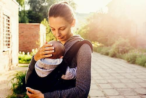 Mama nosi dziecko w chuście.