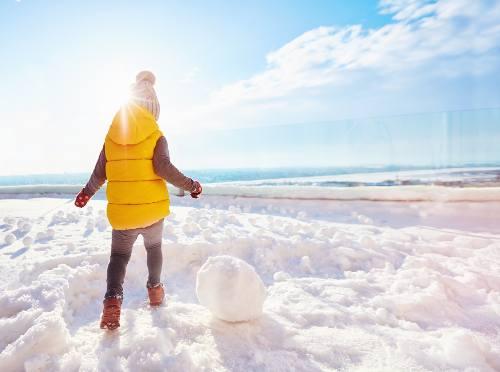 dziecko bawi się na śniegu w słoneczny dzień